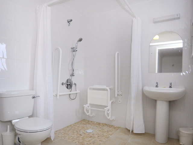Separate large wheelchair accessible wet room with basin, toilet and shower (fitted with pull-down seat and grab rails).