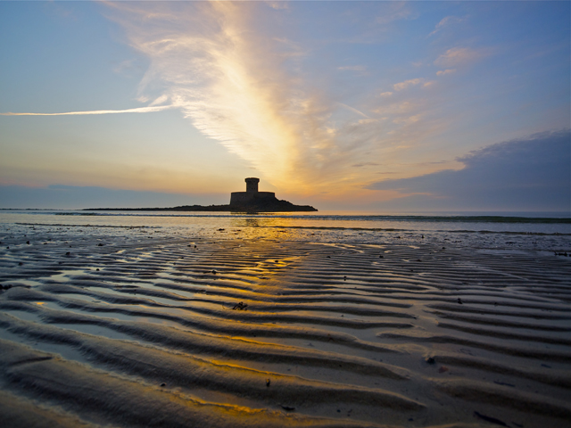 Rocco Tower at sunset is in the middle of St Ouen's Bay