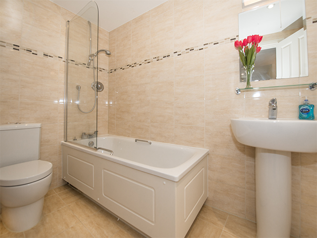 Ensuite bath room with bath with shower over