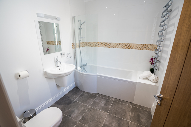 Bathroom located next to downstairs bedroom with shower over bath, sink and toilet