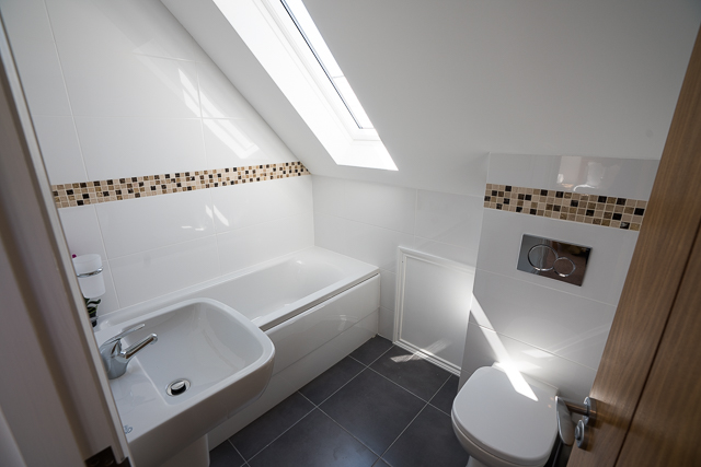 En-suite with shower over bath, sink and toilet