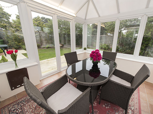 Conservatory with dining table over-looking the lawned garden