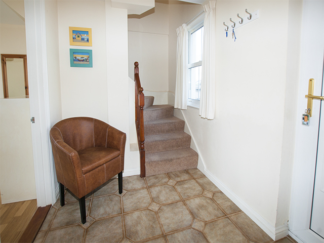 The entrance hall is on the ground floor, the bedrooms are on the beach side of this cottage