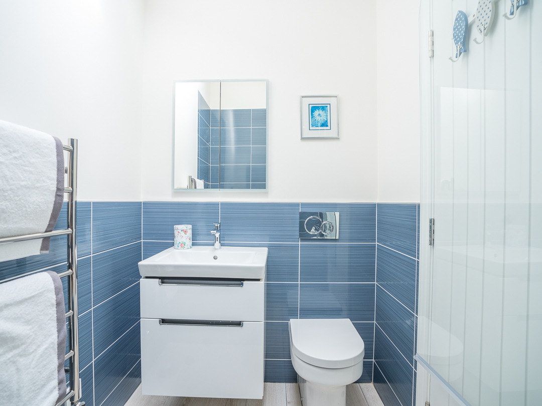 Bathroom with shower over small bath, basin and toilet