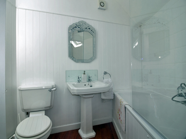 En-suite with shower over bath, basin and WC