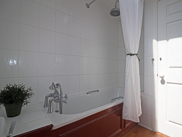 House bathroom with shower over bath, basin and WC