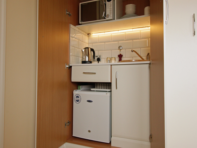 Kitchenette with microwave, toaster, fridge and sink