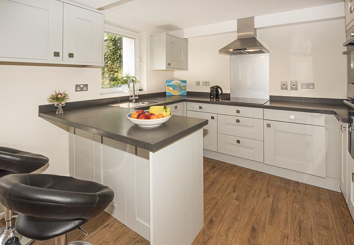 Fully equipped kitchen area with breakfast bar overlooking outdoor seating area