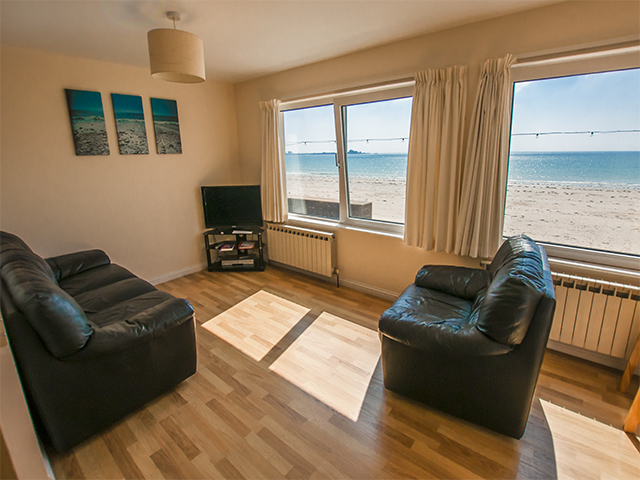 Lounge area of open plan living room overlooking the beach of St Aubin