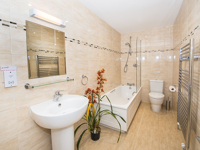 Spacious house bathroom with bath with shower over, basin and toilet