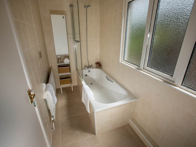 Bathroom with bath with shower over bath and separate basin
