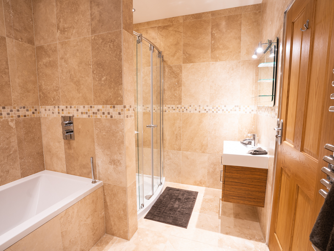 House bathroom with bath, large shower, vanity and WC