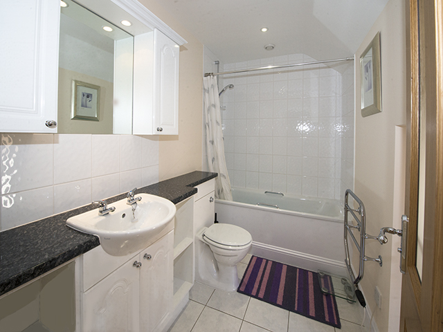 House bathroom with bath with shower over